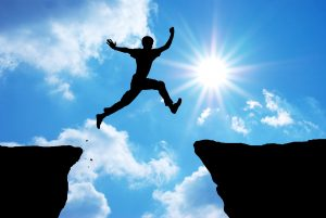 Person jumping across a gap in a rock face with arms outstretched and sun in background - signifying positive change