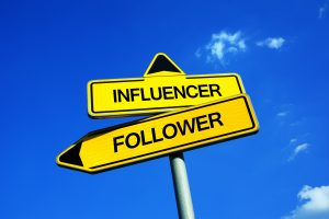 Crossing signs on pole with the words Influencer and Follower - one must lead in order to influence