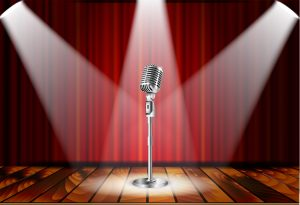 microphone on a stage with a spotlight on it signifying receiving positive attention