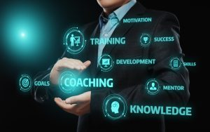 man holding the word coaching surrounded by different words such as success, training and goals.