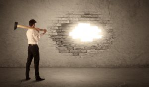 Man knocking hole in wall to let light shine in signifying change