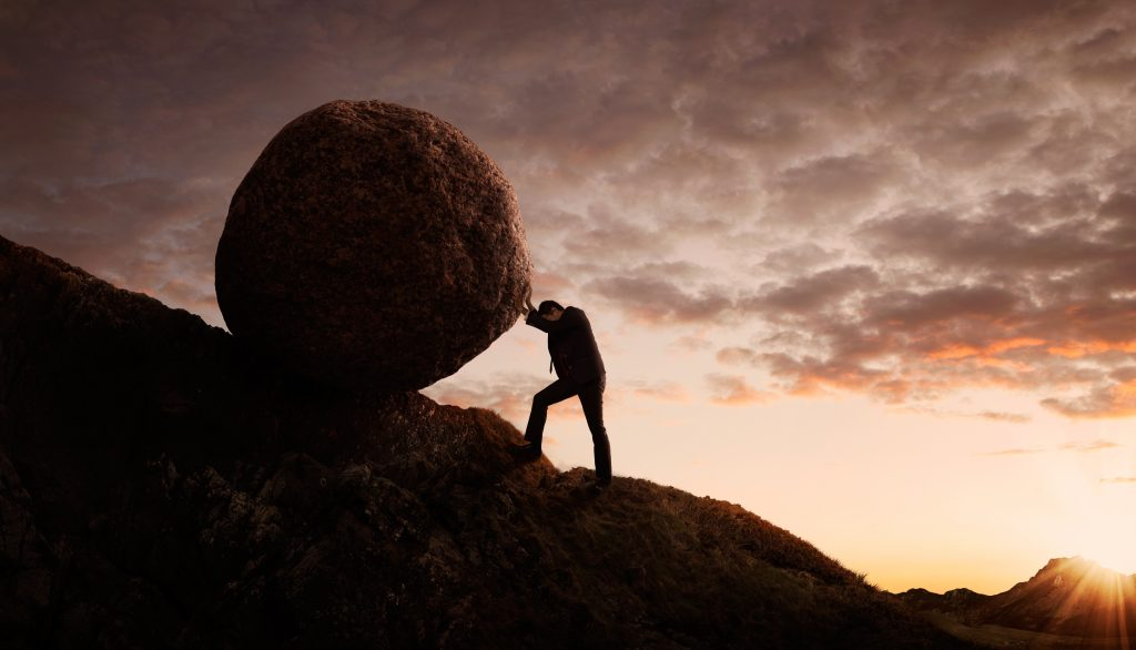 Business person pushing large boulder up hill signifying low motivation