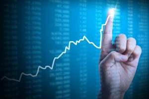 man with finger pointing to graph showing increasing performance